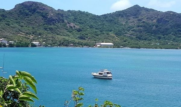 A boat anchored in a natural harbor with mountains in the background