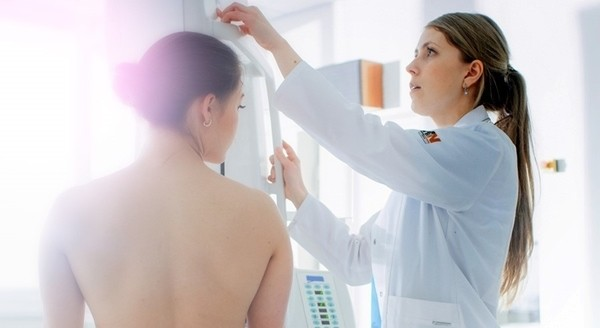 The image shows a woman undergoing a breast scan, under the care of a female doctor.